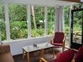 12-De woon- / eetkamer met zicht op terras en bostuin.